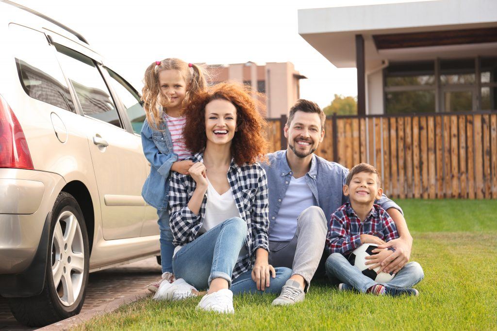 Family smiling by car