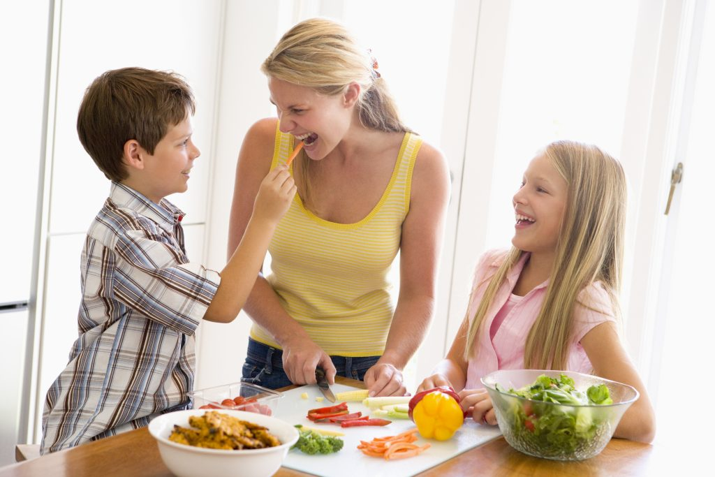 Woman cooking at home with kids to save money