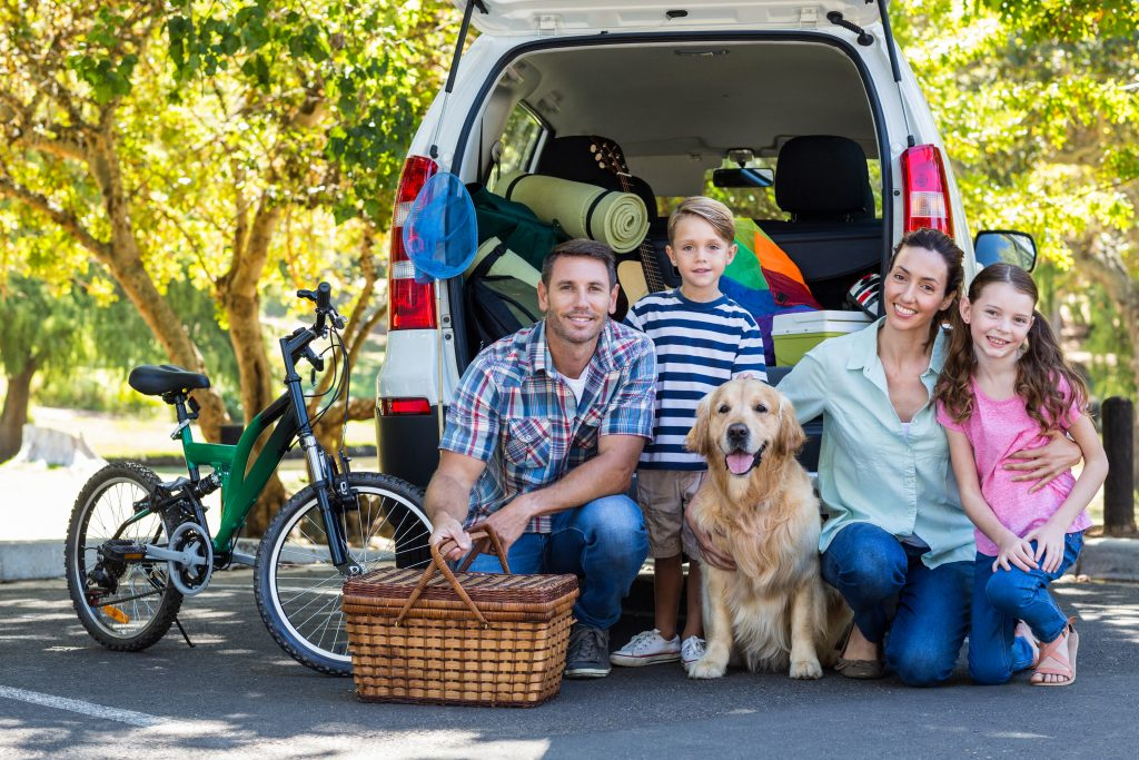 Family and dog going on road trip with picnic basket to save money on food