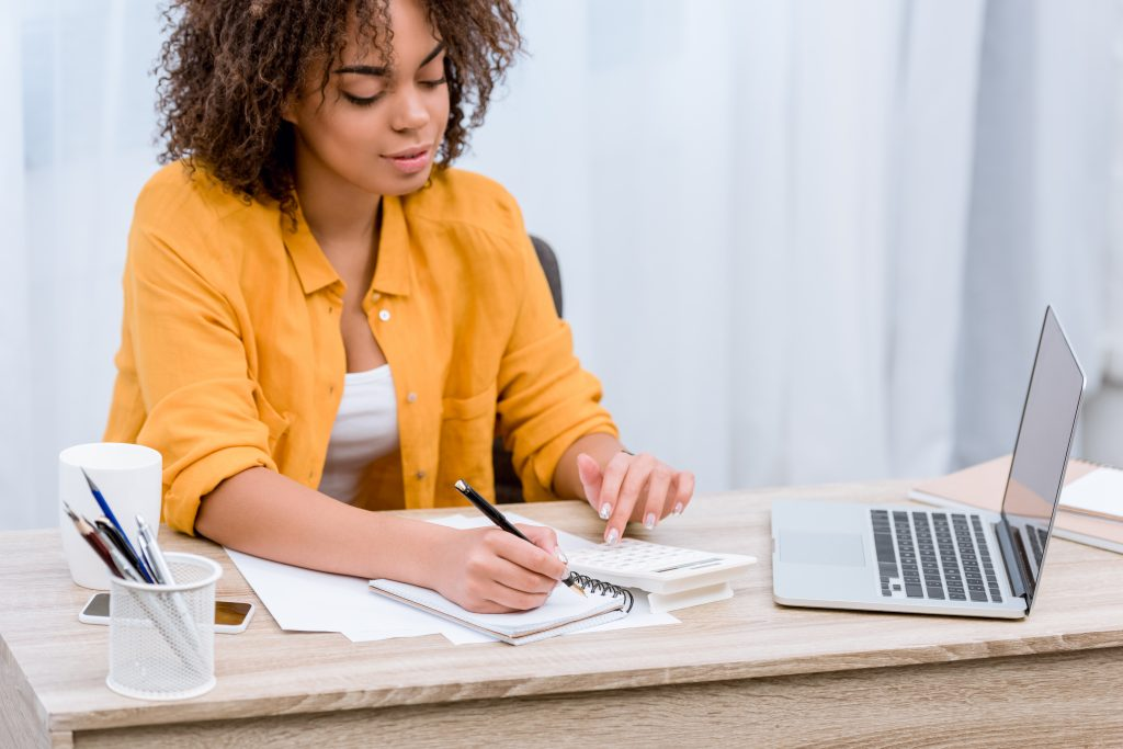 Woman at computer with notebook