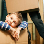Young boy smiling inside a moving box