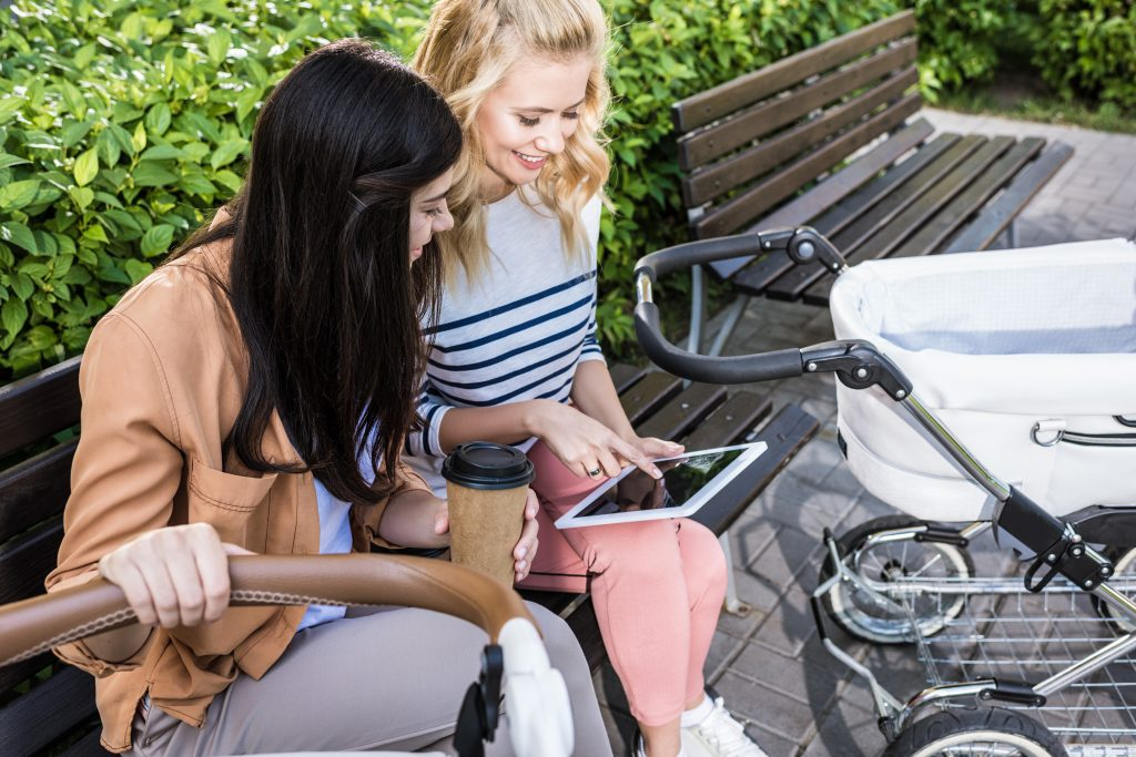Women at park pointing at tablet near a stroller