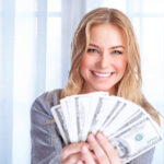 Woman holding money after her no spend challenge