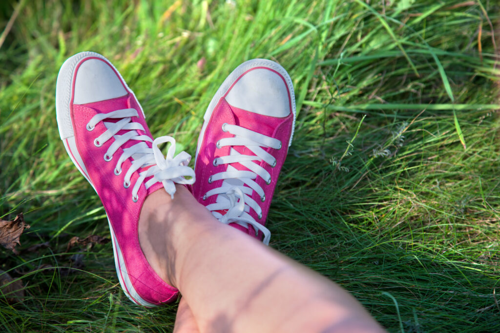 A woman's legs in the grass with pink canvas shoes like Converse.