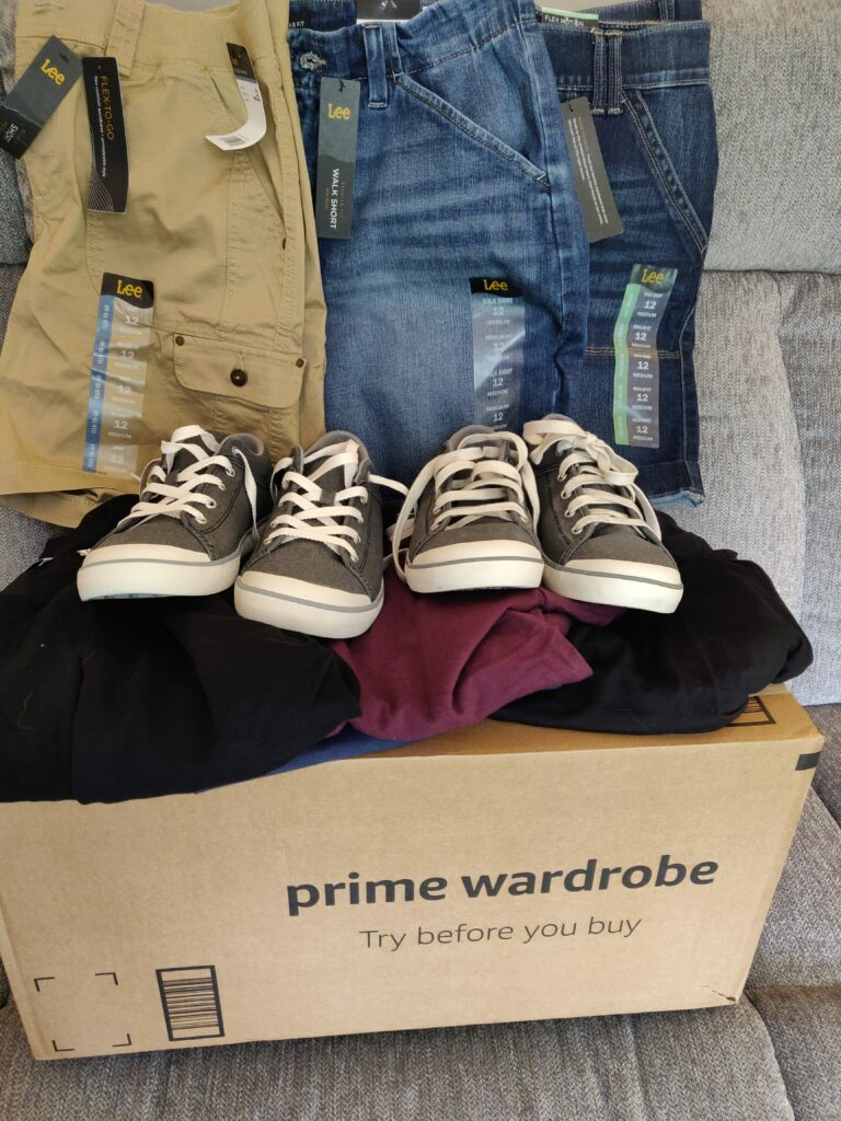 Prime Wardrobe box with clothes and shoes on top of it.