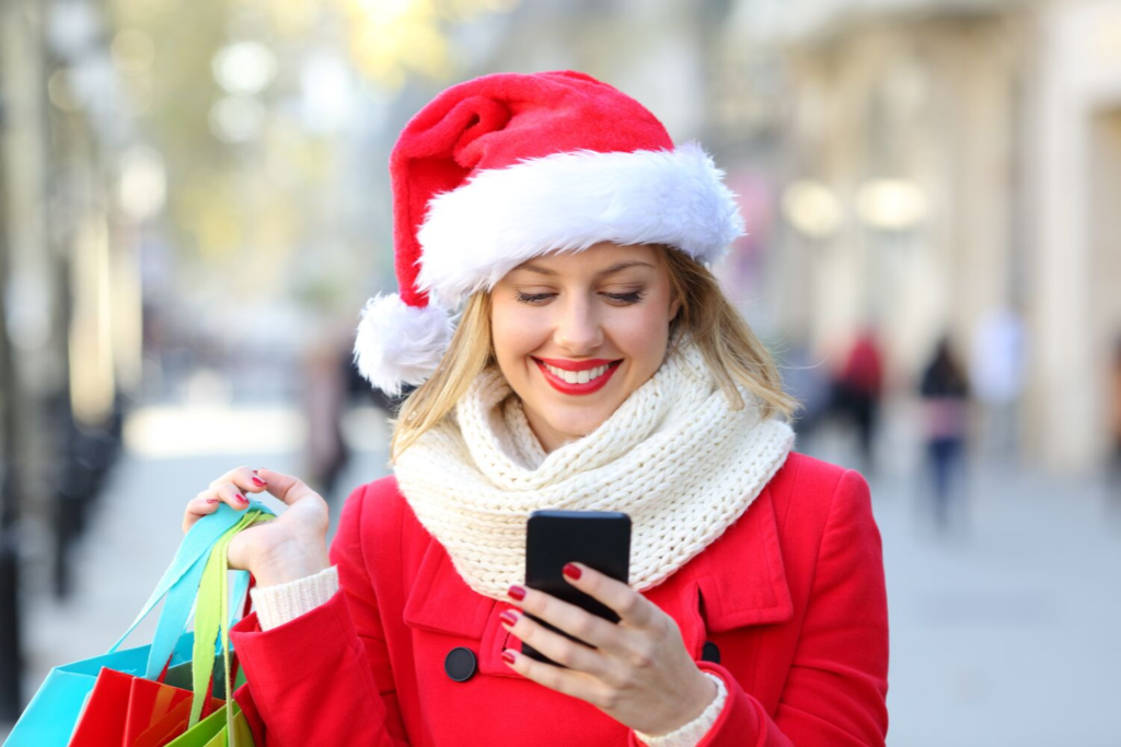 Woman smiling at phone while holding Christmas shopping bags