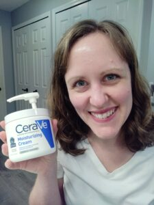 Woman holding tub of Cerave moisturizing cream