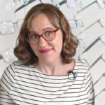 Woman in front of rack of eyeglasses