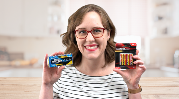 woman holding 2 packs of AA batteries