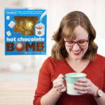 hot chocolate bomb and woman smiling at mug