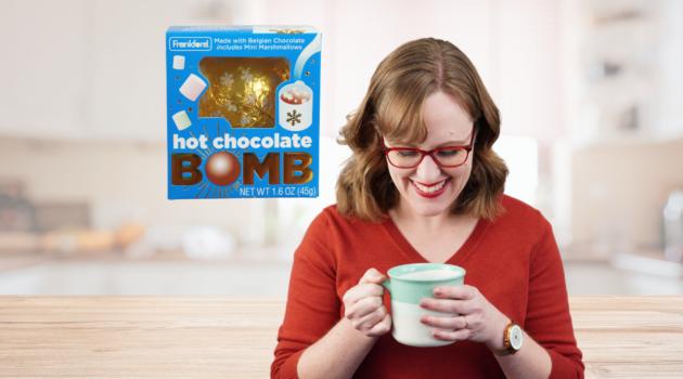 hot chocolate bomb and woman smiling at mug